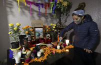 Karen Valencia, lights candles on a Day of the Dead altar for her father Jose Valencia, a male nurse who died from symptoms related to COVID-19, at their home in Mexico City, Sunday, Nov. 1, 2020. The weekend holiday isn't the same in a year so marked by death in a country where more than 90,000 people have died of COVID-19, many cremated rather than buried and with cemeteries forced to close. (AP Photo/Eduardo Verdugo)