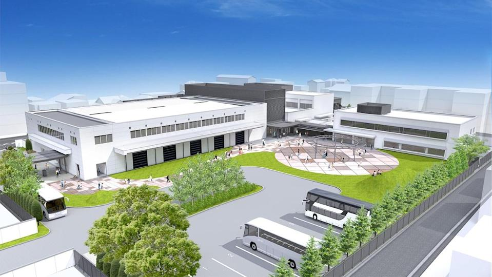 a photo of what the projected Nintendo Gallery will look like upon completion with several tall white buildings, a parking lot, and greenery surrounding the location.
