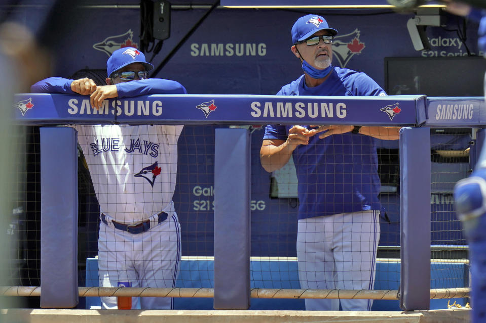 Toronto Blue Jays bench coach Dave Hudgens, right, yells at home plate umpire Junior Valentine after he was ejected during the first inning of a baseball game against the Tampa Bay Rays Monday, May 24, 2021, in Dunedin, Fla. Looking on is manager Charlie Montoyo. (AP Photo/Chris O'Meara)