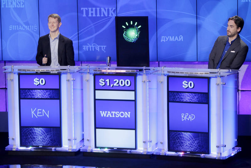 """FILE - In this file photo of Jan. 13, 2011, """"Jeopardy!"""" champions Ken Jennings, left, and Brad Rutter, right, look on as the IBM computer called """"Watson"""" beats them to the buzzer to answer a question during a practice round of the """"Jeopardy!"""" quiz show in Yorktown Heights, N.Y. IBM announced Thursday, Jan. 9, 2014 that it's investing over $1 billion to give its Watson cloud computing system its own business division and a new home in the heart of New York City (AP Photo/Seth Wenig, File)"""
