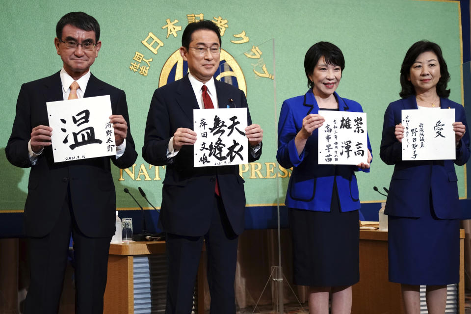 Candidates for the presidential election of the ruling Liberal Democratic Party pose with paper with their sign and words prior to debate session held by Japan National Press club Saturday, Sept. 18, 2021 in Tokyo. The contenders are from left, Taro Kono, the cabinet minister in charge of vaccinations, Fumio Kishida, former foreign minister, Sanae Takaichi, former internal affairs minister, and Seiko Noda, former internal affairs minister. (AP Photo/Eugene Hoshiko, Pool)