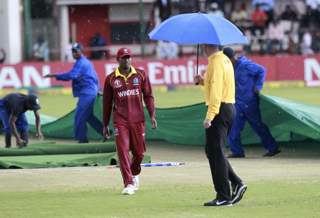 Groundsman cover the pitch after the cricket world cup qualifier match between West Indies and Scotland was rainstopped at Harare Sports Club, Wednesday, March, 21, 2018. Zimbabwe is playing host to the 2018 Cricket World Cup Qualifier matches featuring 10 countries.(AP Photo/Tsvangirayi Mukwazhi)