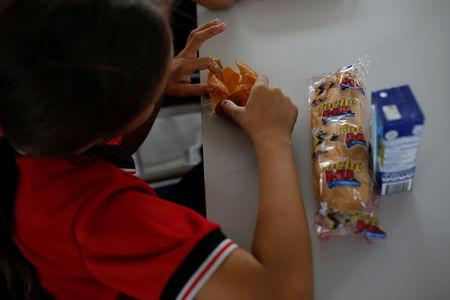 "A child has a snack, as part of a health program of the NGO ""Comparte por una vida"" (Share for a life), at La Frontera school in Cucuta, Colombia February 5, 2019. Picture taken February 5, 2019. REUTERS/Marco Bello"