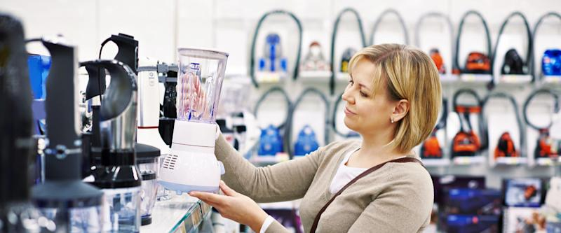 Woman chooses a blender in the store