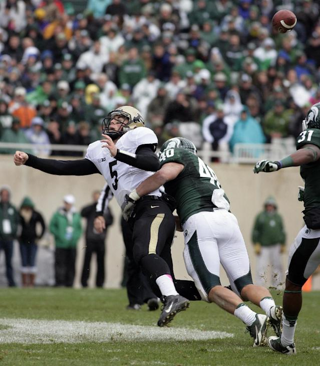 The ball pops loose from Purdue quarterback Danny Etling (5) as he is hit by Michigan State linebacker Max Bullough (40) during the second quarter of an NCAA college football game, Saturday, Oct. 19, 2013, in East Lansing, Mich. At right is Michigan State's Darqueze Dennard (31). The fumble was recovered by Michigan State's Denicos Allen and returned for a touchdown. (AP Photo/Al Goldis)