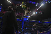 Randy Brown hops atop the octagon fence after winning his UFC 261 mixed martial arts bout, Saturday, April 24, 2021, in Jacksonville, Fla. It is the first UFC event since the onset of the COVID-19 pandemic to feature a full crowd in attendance. (AP Photo/Gary McCullough)
