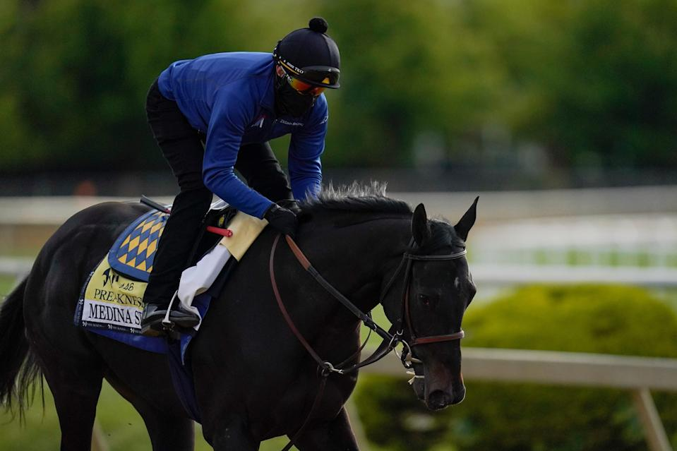Exercise rider Humberto Gomez takes Kentucky Derby winner and Preakness entrant Medina Spirit over the track during a training session ahead of the Preakness Stakes horse race at Pimlico Race Course, Wednesday, May 12, 2021, in Baltimore. (AP Photo/Julio Cortez)