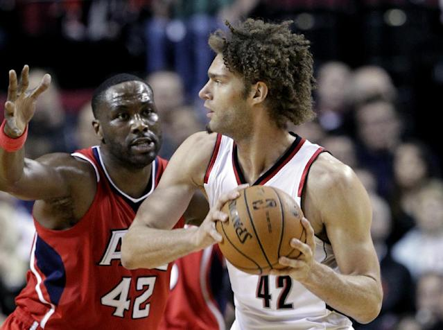 Portland Trail Blazers center Robin Lopez, right, looks to pass against Atlanta Hawks center Elton Brand during the first half of an NBA basketball game in Portland, Ore., Wednesday, March 5, 2014. (AP Photo/Don Ryan)