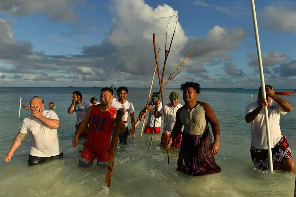 people stand in the water with spears
