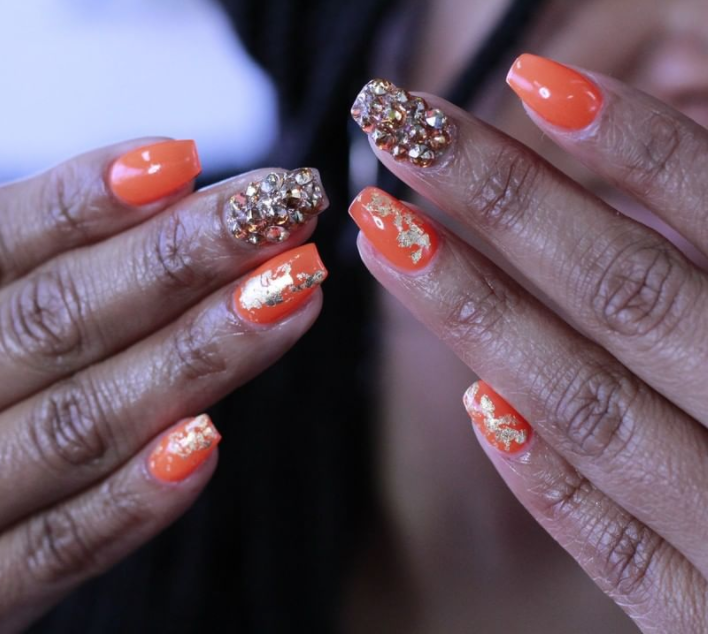 """<p>Feeling fancy? Try layering gold accents, like foil, over an orange nail polish for an elevated Halloween look, like this one from <a href=""""https://www.instagram.com/p/BveBUG_lb9g/"""" rel=""""nofollow noopener"""" target=""""_blank"""" data-ylk=""""slk:nail artist Tahra"""" class=""""link rapid-noclick-resp"""">nail artist Tahra</a>. A little bedazzling doesn't hurt, either. </p><p><a class=""""link rapid-noclick-resp"""" href=""""https://www.amazon.com/Silver-Rainbow-Paillette-Glitter-Decoration/dp/B07PQPVFTM?tag=syn-yahoo-20&ascsubtag=%5Bartid%7C10072.g.33239588%5Bsrc%7Cyahoo-us"""" rel=""""nofollow noopener"""" target=""""_blank"""" data-ylk=""""slk:SHOP GOLD FOIL"""">SHOP GOLD FOIL</a></p>"""