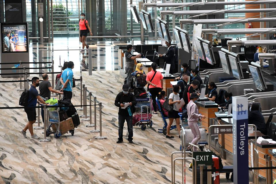Passengers queue at a check-in counter at Changi International Airport in Singapore on June 8, 2020, as Singapore prepares to reopen its borders after shutting them to curb the spread of the COVID-19 novel coronavirus. (Photo by Roslan RAHMAN / AFP) (Photo by ROSLAN RAHMAN/AFP via Getty Images)