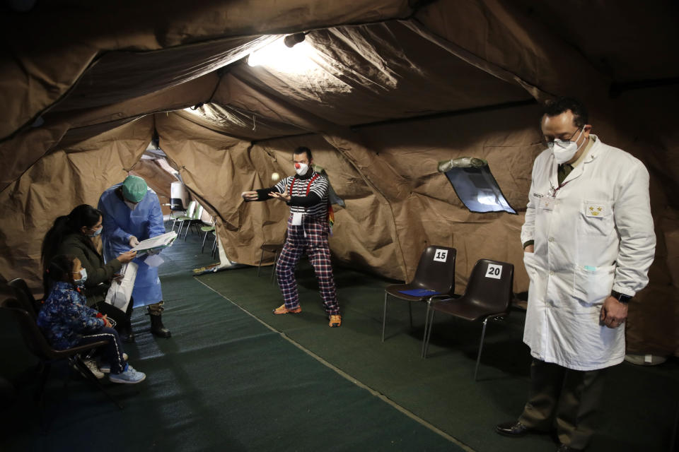 A clown entertains children waiting to receive a flu vaccine in a tent set up at the military hospital in Milan, Italy, Friday, Nov. 20. Health authorities are advising people to vaccine against flu, in a tentative to avoid possible confusion with some symptoms of COVID-19, that could mislead diagnosis. (AP Photo/Luca Bruno)