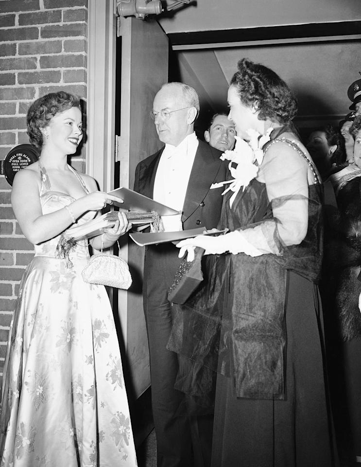 Shirley Temple, left, of the movies, hands a program to Secretary of the Treasury John W. Snyder and his wife Carrie Evelyn Snyder as they arrive for President Truman's inaugural ball in Washington, Jan. 20, 1949. (AP Photo)