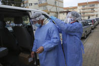 Municipal workers remove their protective gear after collecting presidential election ballots from an elderly care home in Montijo, south of Lisbon, Tuesday, Jan. 19, 2021. For 48 hours from Tuesday, local council crews are collecting the votes from people in home quarantine and from residents of elderly care homes ahead of Sunday's presidential election. (AP Photo/Armando Franca)