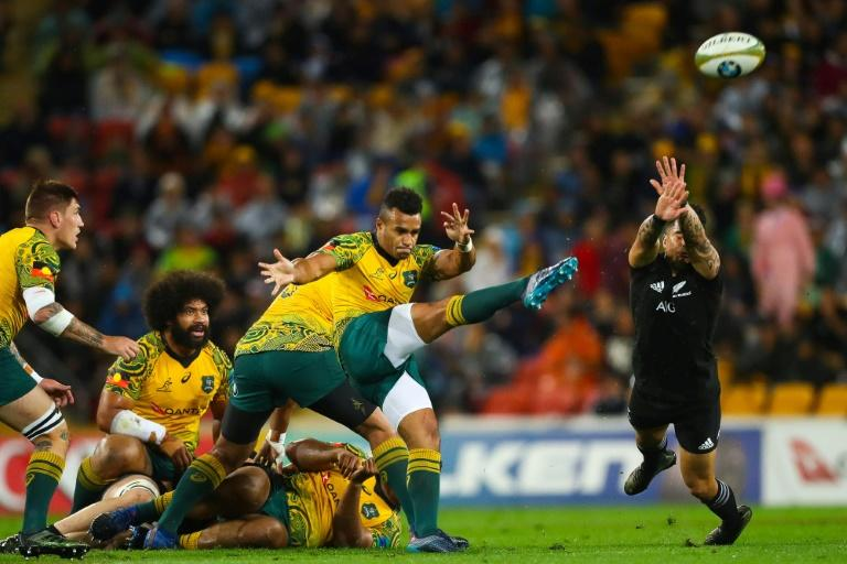 Will Genia of Australia's Wallabies (front L) kicks ahead as Rieko Ioane of New Zealand's All Blacks attempts to charge down during their match in Brisbane on October 21, 2017