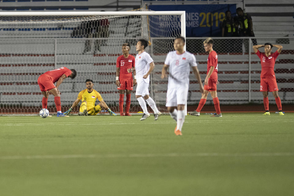 Singapore players react with dismay after conceding a late winning goal to Vietnam at the SEA Games football competition. (PHOTO: SNOC/Lim Weixiang)