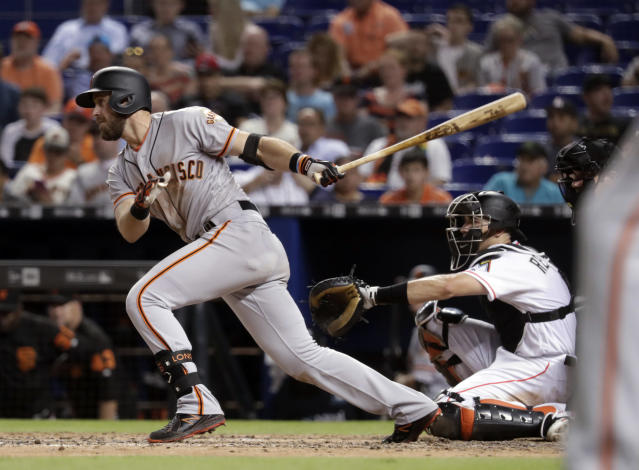 San Francisco Giants' Evan Longoria, left, watches his RBI single to score Buster Posey during the seventh inning of a baseball game against the Miami Marlins, Wednesday, June 13, 2018, in Miami. The Marlins won 5-4. At right is Miami Marlins catcher J.T. Realmuto. (AP Photo/Lynne Sladky)