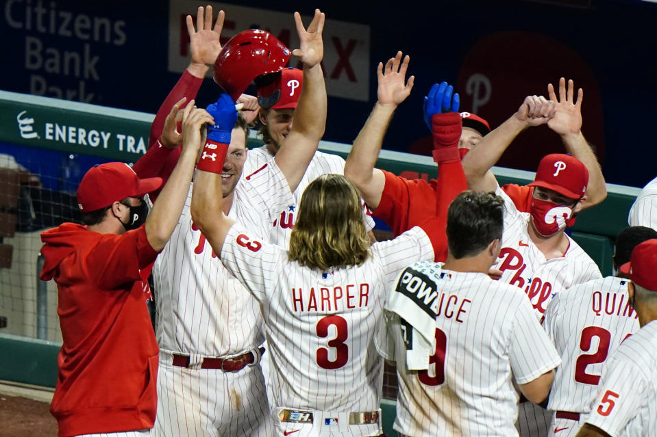 Philadelphia Phillies' Bryce Harper, center, celebrates with teammates after hitting the game-winning RBI-single off New York Mets pitcher Seth Lugo during the ninth inning of a baseball game, Friday, Aug. 14, 2020, in Philadelphia. Philadelphia won 6-5.(AP Photo/Matt Slocum)