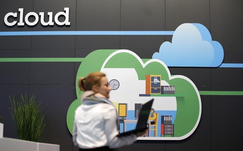 A women holds her laptop as she walks in front of a cloud computing logo at the booth of IBM during preparations for the CeBIT trade fair in Hanover