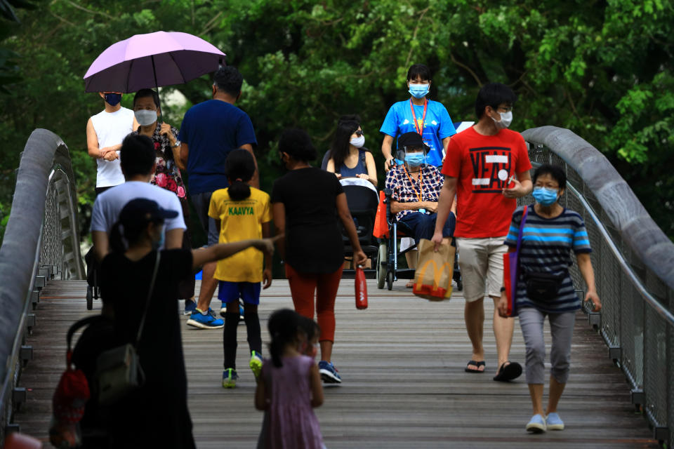 People wearing protective mask walk at a park on September 4, 2021 in Singapore. (Photo by Suhaimi Abdullah/NurPhoto via Getty Images)
