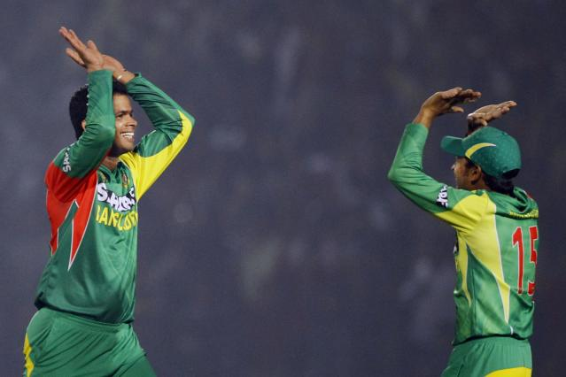 Bangladesh's Abdur Razzak, left, and captain Mushfiqur Rahim celebrate the dismissal of India's Shikhar Dhawan during the Asia Cup one-day international cricket tournament between them in Fatullah, near Dhaka, Bangladesh, Wednesday, Feb. 26, 2014. (AP Photo/A.M. Ahad)