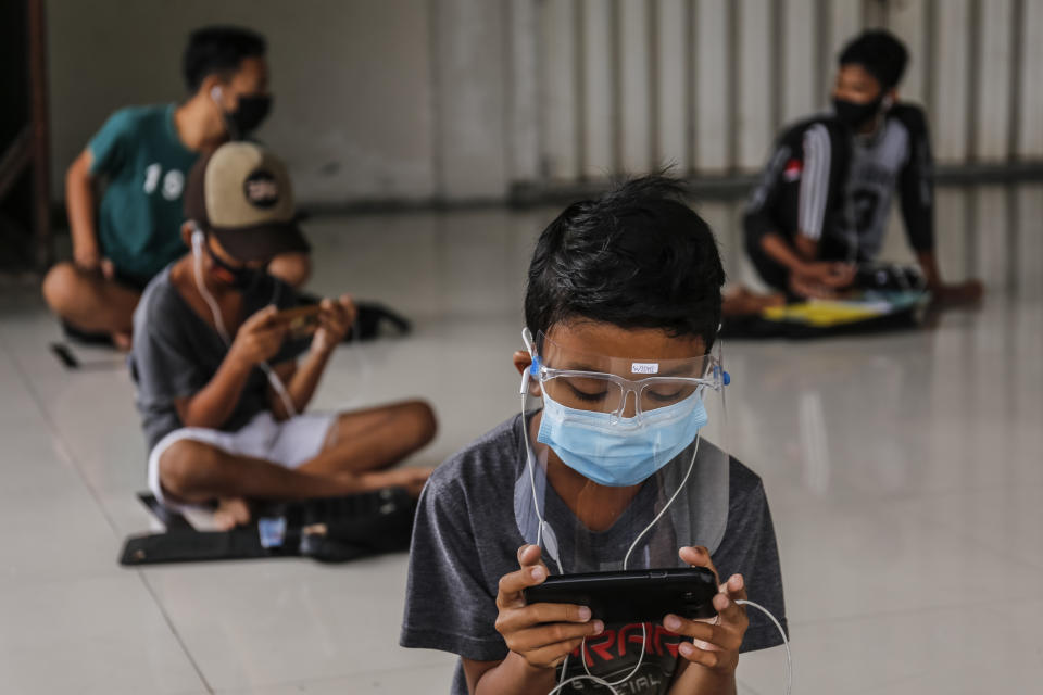 Students use smartphones to work on online school assignments using free internet network while practicing physical distancing at a public hall in Ubung Kaja Village, Denpasar, Bali, Indonesia on July 21, 2020. (Photo by Johanes Christo/NurPhoto via Getty Images)