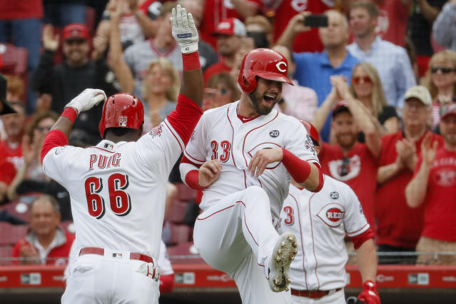 Cincinnati Reds' Yasiel Puig (66) celebrates with Jesse Winker (33) after hitting a two-run home run off Atlanta Braves starting pitcher Kevin Gausman in the first inning of a baseball game, Tuesday, April 23, 2019, in Cincinnati. (AP Photo/John Minchillo)