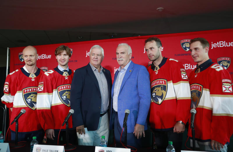 FILE - In this July 2, 2019, file photo, Florida Panthers President of Hockey Operations & General Manager Dale Tallon, third from left, and head coach Joel Quenneville, third from right, pose with new players Anton Stralman, left, Sergei Bobrovsky, second from left, Brett Connolly, second from right, and Noel Acciari, right, after a news conference in Sunrise, Fla. With Tampa Bay, Boston, the Toronto Maple Leafs and refueled Florida Panthers, the Atlantic Division looks like murderers row. (AP Photo/Wilfredo Lee, File)