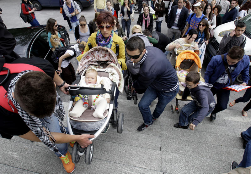 Bosnians and their babies protest in front of the Bosnian parliament building in Sarajevo, Thursday, June 6, 2013. Nearly 3,000 people formed a chain around Bosnia's parliament Thursday, saying they won't let politicians go home until they start doing their jobs instead of keeping the country paralyzed with ethnic bickering. What started as a small protest over a new law on personal identification numbers the day before has grown into a blockade of the building, with more people joining the protest every hour. (AP Photo/Amel Emric)