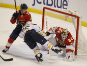 Florida Panthers goaltender James Reimer (34) covers the puck as Buffalo Sabres center Seth Griffith (25) attempts a shot against him and defenseman Mark Pysyk (13) during the third period of an NHL hockey game, Friday, March 2, 2018, in Sunrise, Fla. (AP Photo/Wilfredo Lee)
