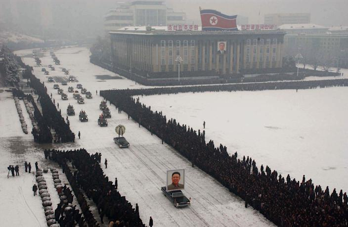 A portrait of late North Korean leader Kim Jong Il is carried past mourners during his funeral procession through the streets of Pyongyang, North Korea Wednesday Dec. 28, 2011.