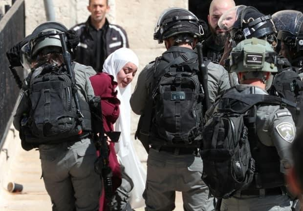 Israeli security members detain a Palestinian woman at Damascus Gate just outside Jerusalem's Old City during a demonstration held by Palestinians to show solidarity amid Israel-Hamas fighting.