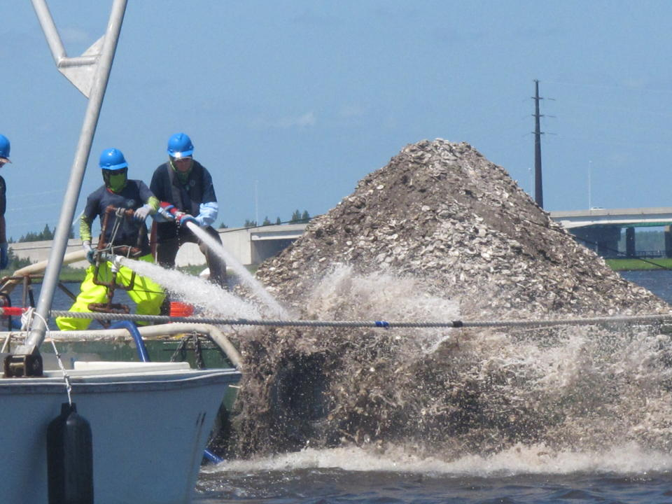 In this June 29, 2021 photo, workers aboard a barge laden with 680 bushels of clam and oyster shells use high-pressure hoses to blast them into the Mullica River in Port Republic, N.J. The shells are collected from restaurants in Atlantic City, dried, and placed into the river where they become the foundation for new oyster colonies as free-floating baby oysters attach to them and start to grow. Communities around the world are running similar shell recycling programs. (AP Photo/Wayne Parry)