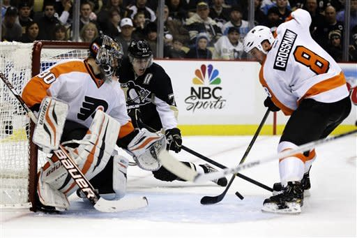 Pittsburgh Penguins center Evgeni Malkin (71) looks for the puck against Philadelphia Flyers goalie Ilya Bryzgalov (30) and defenseman Nicklas Grossmann (8) in the second period of an NHL hockey game in Pittsburgh, Wednesday, Feb. 20, 2013. (AP Photo/Gene J. Puskar)