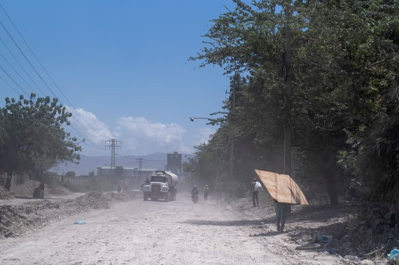 A fuel tanker drives on an unpaved road