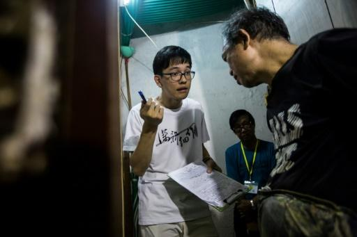 Volunteer Max Leung (left) speaks with a resident of a subdivided flat who requested for his fridge to be repaired