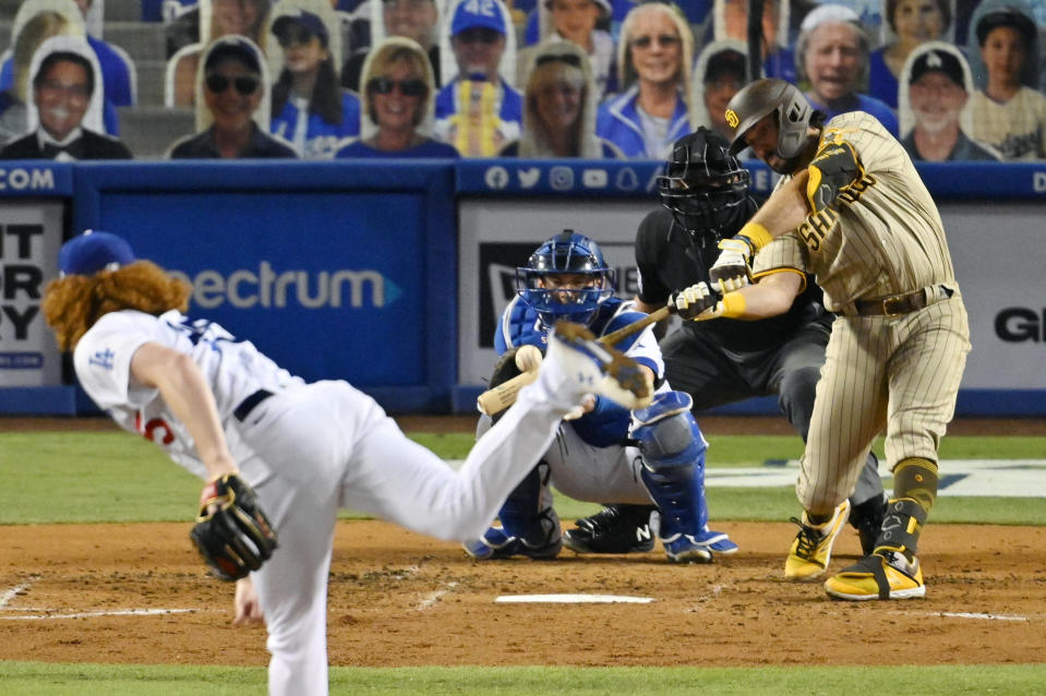 San Diego Padres' Austin Hedges, right, hits a solo home run as Los Angeles Dodgers starting pitcher Dustin May, left, and catcher Will Smith, second from left, watch along with home plate umpire John Libka during the fifth inning of a baseball game Monday, Aug. 10, 2020, in Los Angeles. (AP Photo/Mark J. Terrill)