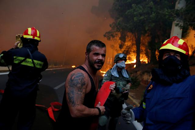 <p>Firefighters, soldiers and local residents carry a hose as a wildfire burns in the town of Rafina, near Athens, Greece, July 23, 2018. (Photo: Costas Baltas/Reuters) </p>