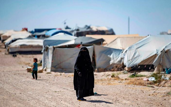 A woman walks in the Kurdish-run al-Hol camp in the al-Hasakeh governorate in northeastern Syria on August 25, 2020, where families of Islamic State (IS) foreign fighters are held.