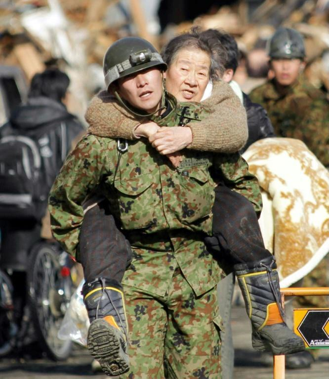 A soldier carries an elderly woman as people are evacuated to a shelter in Miyagi prefecture the day after the tsunami
