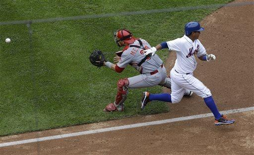 New York Mets' Ruben Tejada, right, easily beat the throw to Cincinnati Reds catcher Devin Mesoraco to score a run during the fifth inning of a baseball game at Citi Field Wednesday, May 22, 2013, in New York. (AP Photo/Seth Wenig)