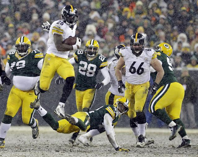 Pittsburgh Steelers' Le'Veon Bell (26) leaps over Green Bay Packers' Morgan Burnett during the second half of an NFL football game Sunday, Dec. 22, 2013, in Green Bay, Wis. (AP Photo/Mike Roemer)