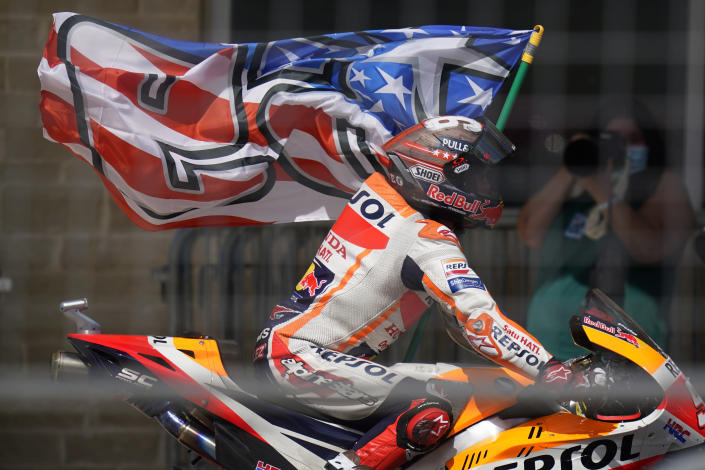 Spain's Marc Marquez carries a flag as he celebrates his win at the MotoGP Grand Prix of the Americas motorcycle race at Circuit of the Americas, Sunday, Oct. 3, 2021, in Austin, Texas. (AP Photo/Eric Gay)