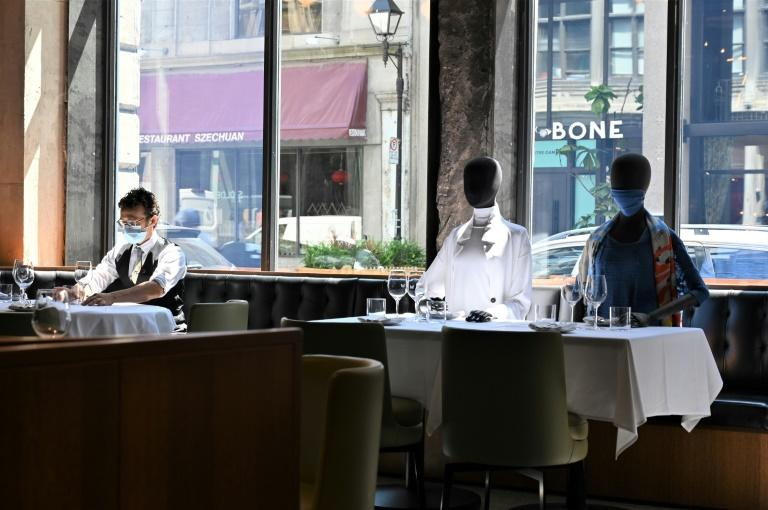 A server (L) wearing a facemask adjusts glasses on a table near mannequins placed to provide social distancing at a Montreal restaurant on July 10, 2020 amid the pandemic; the mannequins' clothes are sold, with profits going to charity