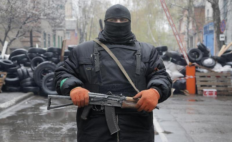 A pro-Russian gunman stands guard at a seized police station in the eastern Ukraine town of Slovyansk on Sunday, April 13, 2014. Pro-Moscow protesters have seized a number of government buildings in the east over the past week, undermining the authority of the interim government in the capital, Kiev. (AP Photo/Efrem Lukatsky)