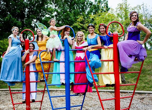 "The magical bridal party dressed as Disney characters: From left to right: Cinderella, Alice in Wonderland, Belle, Tinkerbell, Giselle, Sleeping Beauty, Princess Jasmine, Snow White, and Megara. They walked down the aisle to an instrumental version of ""Under the Sea."""