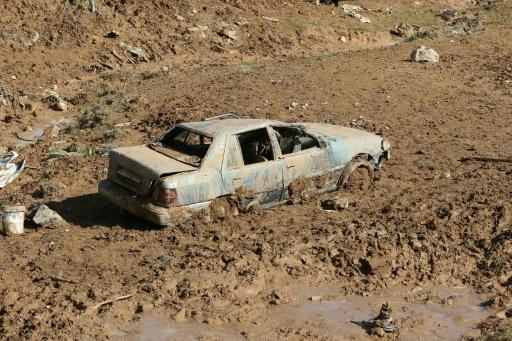 A picture taken on November 10, 2018 shows a car submerged in mud following flash floods in the city of Madaba near the capital Amman