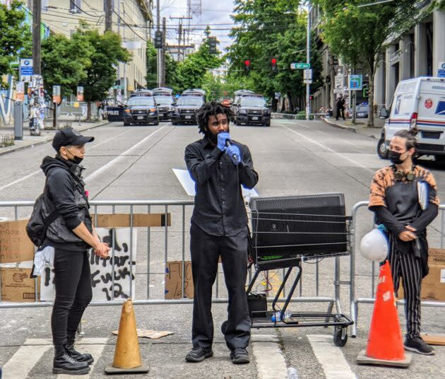 Activists Malcolm Frankson (speaking) and Jack Eppard Barajas (right) discuss police reforms with a crowd of protesters in Seattle's Capitol Hill neighborhood. Social distancing, masks and gloves are among measures being taken to avoid spreading coronavirus. (GeekWire Photo / Monica Nickelsburg)