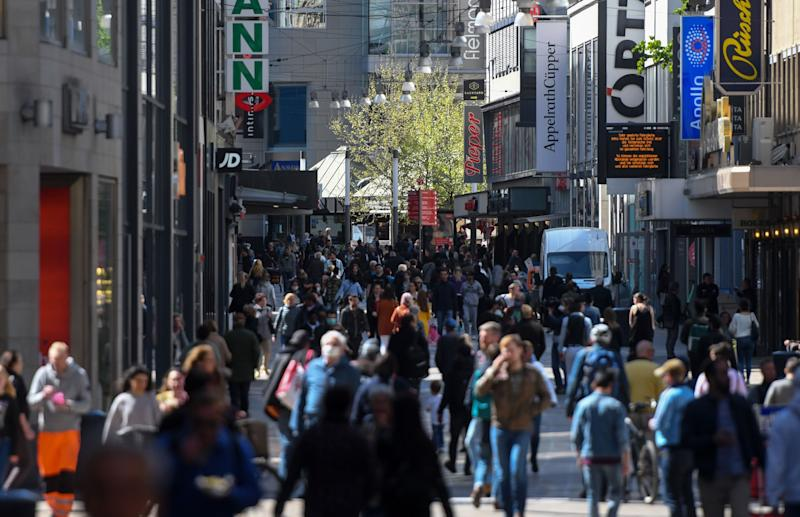 People walk past shops on a pedestrian street in Dortmund in Dortmund, western Germany, on April 20, 2020, during the novel coronavirus COVID-19 pandemic. - Some small shops in Germany reopened on Monday as the country took a cautious step toward returning to normal, though Chancellor Angela Merkel issued a stark warning against complacency in the face of the pandemic. (Photo by Ina FASSBENDER / AFP) (Photo by INA FASSBENDER/AFP via Getty Images)