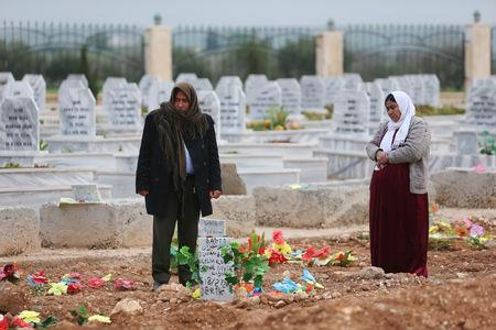 A woman reacts at a grave of her daughter, an SDF fighter killed during fightings with Islamic State militants, at a cemetery in Kobani, Syria April 4, 2019. REUTERS/Ali Hashisho